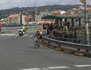 Un corredor enfilando, tras la moto policial que le abre el camino, el Puente de la Barca, para acceder al final de etapa en Pontevedra, Vuelta a España 2012