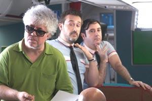 """Pedro Almodóvar en un momento de la filmación de """"Los amantes pasajeros"""". Detrás, dos de los protagonistas, Javier Cámara y Carlos Areces, preparando una escena"""