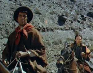 """La pareja protagonista galopando en el filme """"El Camino del Gaucho"""" producido por Hollywood en los campos y serranías de Argentina."""