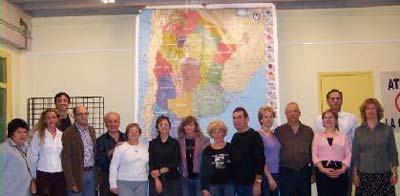Asociados y comisión directiva de la Asociación Cultural Argentina de Manresa junto al mapa de la República Argentina