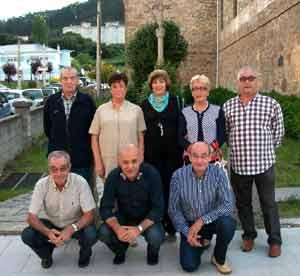 María Gema López Abda, inmigrante gallega en Argentina, posando con familiares suyos en una visita a Galicia. Detrás, un cruceriro típico de estas tierras