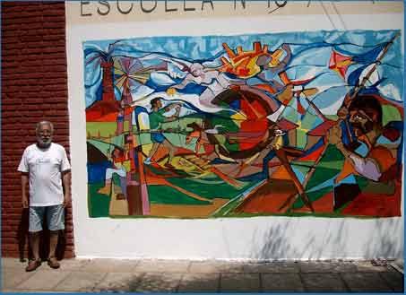 El muralista argentino Jorge Cruz Crinejo, de la ciudad de Córdoba, junto a una de sus obras