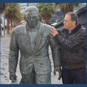 Enrique Migliarini, odontólogo y cantor de tango argentino que reside en Vigo, España, junto a la estatua del emigrante gallego en el puerto vigués de la provincia de Pontevedra