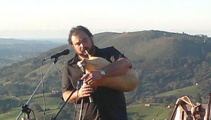 Pablo Mezzelani, cantante y músico argentino, tocando la gaita búlgara con el paisaje de Cantabria, España, de fondo