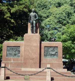 Monumento a Manuel Belgrano como abogado y edil, en la Plaza Belgrano, Buenos Aires, Argentina. En portada: busto esulpido en Córdoba, Argentina, por el artista cordobés Carlos Benavidez